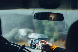Driver showing she is distracted by passenger taking a photo of them which could cause an accident.Photo by Omar Lopez on Unsplash