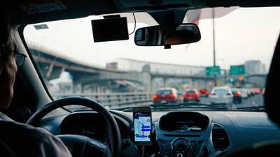 driver in a car shows to be distracted on the expressway from GPS on his phone. Photo by: Dan Gold on Unsplash
