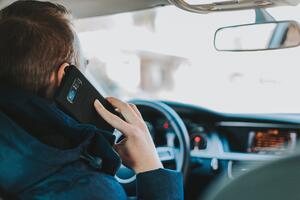 a man driving but is distracted by talking on the phone and causing an accident . Photo by Alexandre Boucher on Unsplash