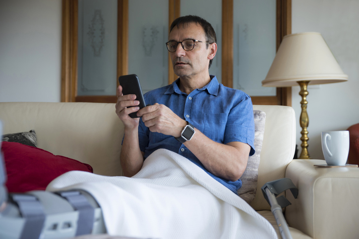 A man sitting on a couch with his injured leg in a cast raised up as he scrolls through messages from his insurance adjuster on his phone