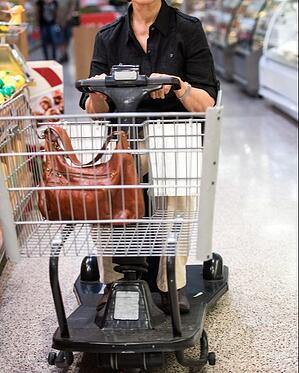 Elderly woman in grocery store driving a motorized shopping cart scooter that has the capability of causing serious injury if not handled correctly