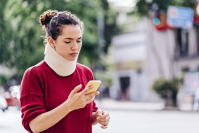 woman with neck brace on looking at phone confused as to why insurance adjusters won't pay her compensation until she signs release forms