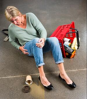 A woman lying on the floor of a grocery store with her groceries everywhere and coffee spilled after getting hit by a motorized shopping scooter.