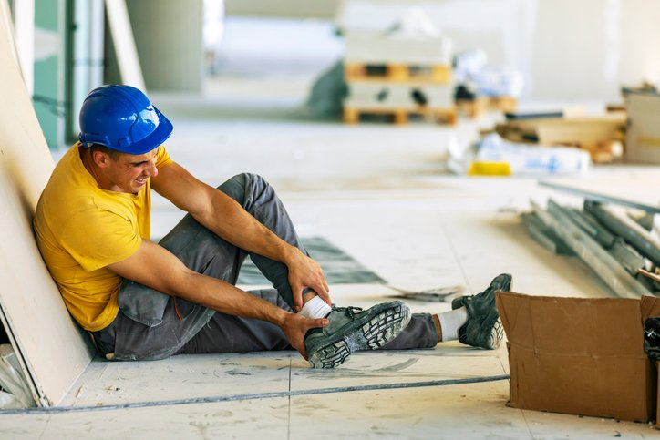 Construction worker grabbing his ankle in pain from an injury on the job